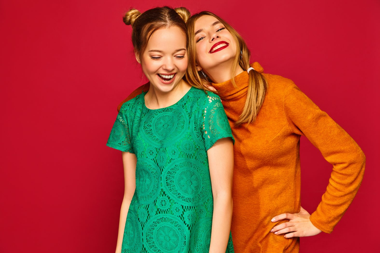 Two young beautiful blond smiling hipster girls posing in trendy summer clothes. Carefree women isolated on red background. Positive models going crazy and hugging