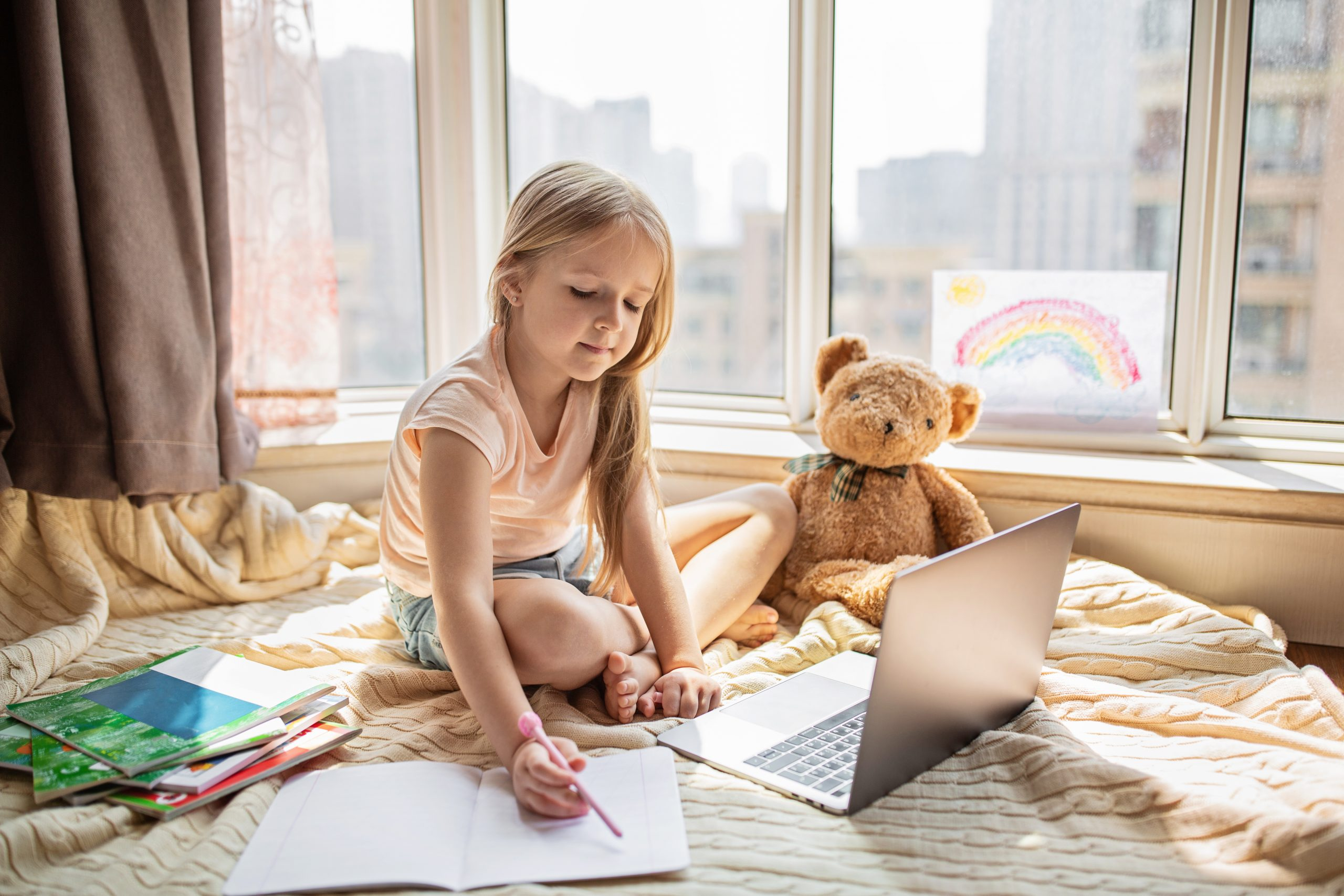 Pretty schoolgirl studying homework during her online lesson at home, social distance during quarantine covid-19, self-isolation, online education concept, home schooler. Workplace in living room.